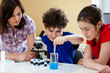 Kids examining preparation under the microscope
