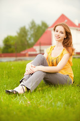 Beautiful girl sits on lawn