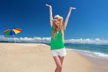 久高島のビーチで大空に向かって両手を広げる女性