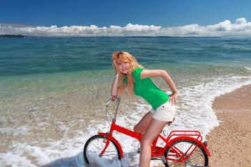 久高島のビーチでサイクリングを楽しむ笑顔の女性