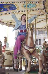Joyful girl on the carousel