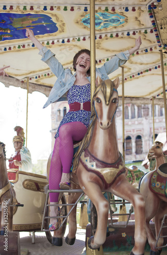 Joyful girl on the carousel