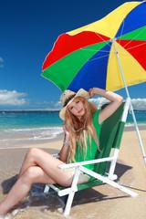 ビーチチェアに座り寛ぐ笑顔の女性