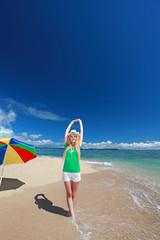 久高島の波打ち際で背伸びをする笑顔の女性