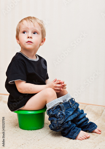 Boy is sitting on the pot