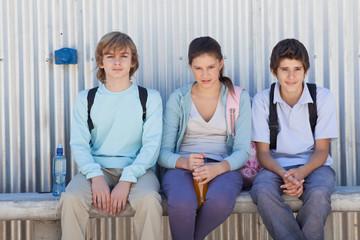 Three children sitting side by side on bench