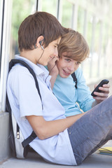 Two boys sitting with earbuds and cell phone