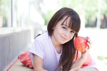Girl lying outdoors holding apple