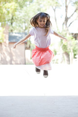 Girl skipping rope outdoors