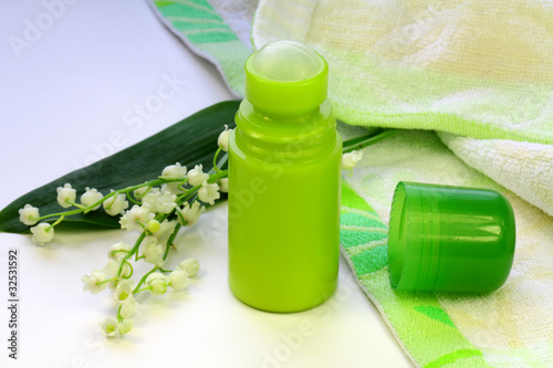 Lily of the valley, a towel and a deodorant on the table