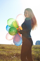 young beautiful woman with balloons into the field against the s