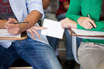 Two students exchanging sheet of paper in classroom