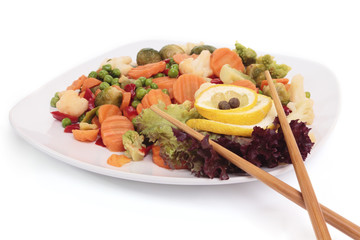 Salad on a plate with vegetables and wooden sticks