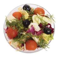 Salad on a glass plate with vegetables. Isolated on white