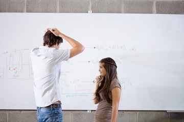 Two students standing at whiteboard with formula
