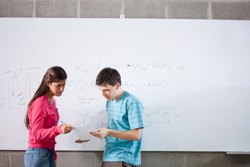 Two serious students standing with test at whiteboard