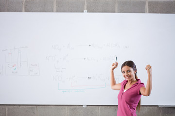 Cheering student standing at whiteboard with formula