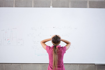Frustrated student standing at whiteboard with formula