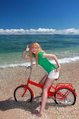 自転車に乗ってガッツポーズしている笑顔の女性