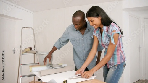 Couple choosing new wallpaper for room