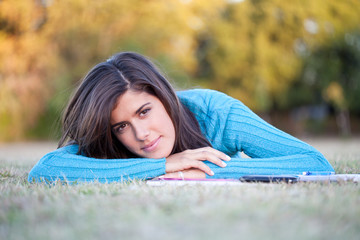 Student lying in grass with cell phone and notebook