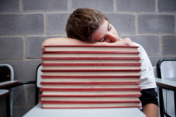 Schoolboy sleeping on stack of books