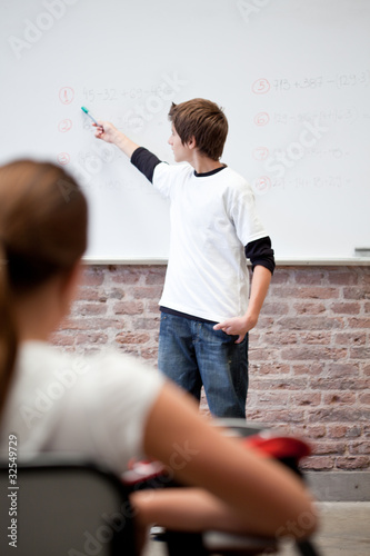 Schoolboy standing at whiteboard with numbers