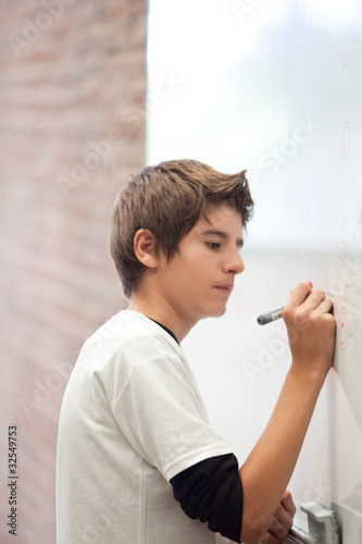 Schoolboy in classroom writing on whiteboard