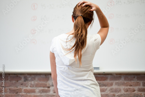 Frustrated schoolgirl looking at whiteboard