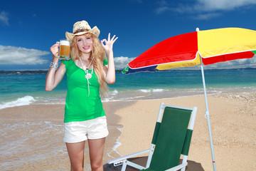 久高島の波打ち際でビールを飲んでいる笑顔の女性