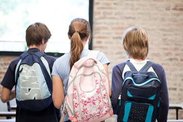 Three schoolchildren wearing backpacks