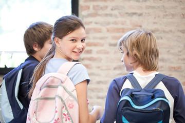 Three schoolchildren wearing backpacks