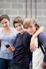 Three schoolchildren with cell phone and MP3 player