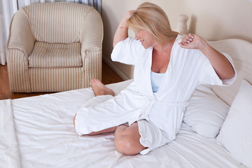 Mature woman in bathrobe sitting in bed