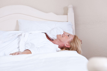 Smiling mature woman lying in bed