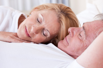 Mature couple sleeping in bed