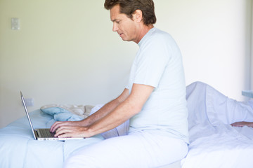 Mature man using laptop in bed