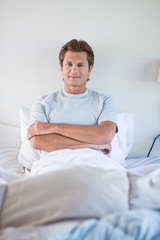 Mature man in bed with arms crossed