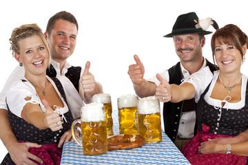 Bayrische Mädchen und Männer mit Maß Bier zeigen Daumen oben