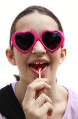 Young teen girl with lollipop and heart shaped sunglasses