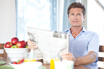 Mature man reading newspaper at table