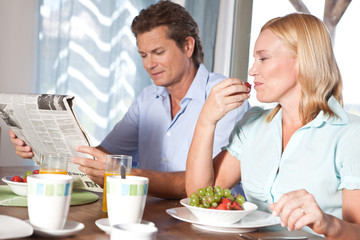 Mature couple at breakfast table with newspaper and fruit