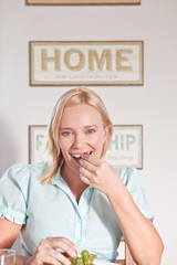 Woman eating fruit at home