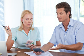 Mature couple at home paying bills