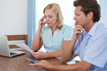 Serious mature couple at home paying bills
