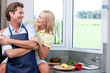 Woman embracing husband with apron in kitchen