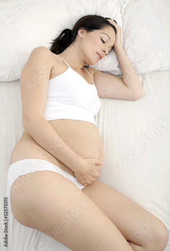 Unhappy pregnant woman laying in bed