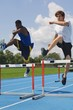 Men Running Down A Track And Jumping Over Hurdles