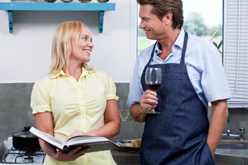 Mature couple with red wine and cookbook in kitchen