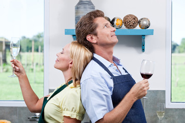 Mature couple in kitchen with red wine and champagne